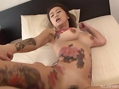 Two horny guys use and decry a tattooed Japanese MILF